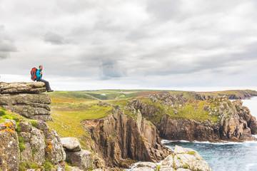 Man sitting on a rock cliff enjoying the view