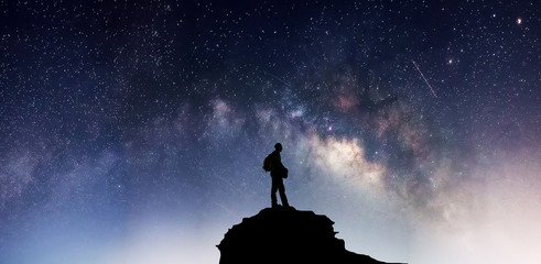 Travelers stand on a mountain on the Milky Way background.
