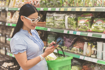 Cheerful woman typing on phone in supermarket