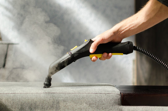 Hand cleaning a  sofa with a steam cleaner. Home cleaning concept.