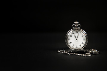 Monochrome image of an isolated pocket watch on a black background