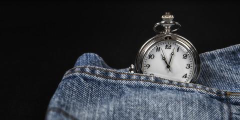 Color image of a pocket watch in a denim pocket