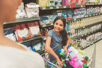 Brightly smiling female child doing shopping with mom