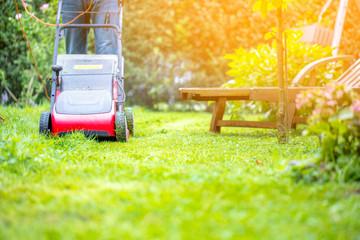 Mann Mäht rasen im eigenem Garten
