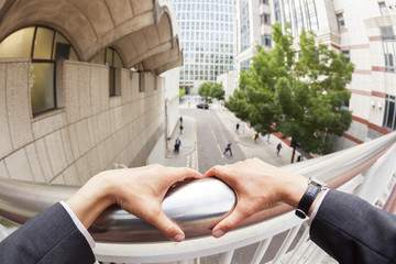 Personal perspective of a businessman holding onto railings