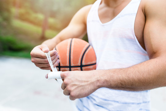 Young athletic man fixing injury on basketball court