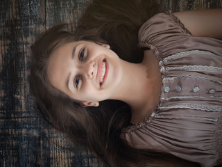 Beautiful girl lying on the floor. Long brown hair. With a joyful smile