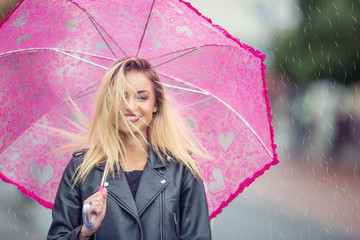 Attractive young woman with pink  umbrella in the rain and strong wind. Girl with umbrella in autumn weather
