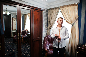 Portrait of a stunning groom dressing up for the wedding and getting ready in his room.