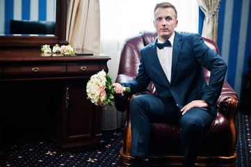 Portrait of a handsome groom posing with bridal bouquet in his cool room on the wedding day.