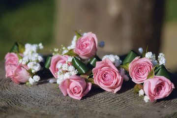 Flower arrangement for wedding centerpiece featuring small pink roses and baby's-breath, positioned on a tree stump, with shallow depth of field