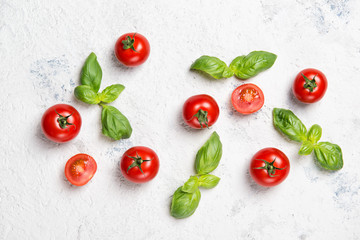 Fresh cherry tomatoes with basil leaves on a stone table, vegetable pattern, top view
