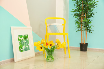 Comfortable yellow chair and decorative elements near wall in modern room