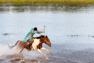 Young Mongolian horseman rides at full gallop on the river