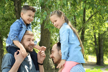 Smiling gay couple with children in park