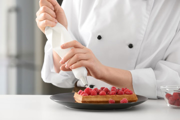 Female chef decorating dessert in kitchen, closeup