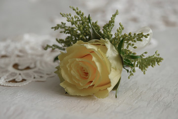Wedding accessories: fresh yellow rose small bouquet for buttonhole used for groom and wedding guests positioned on a white cloth, in natural light