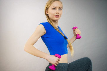 Teenage woman working out at home with dumbbell