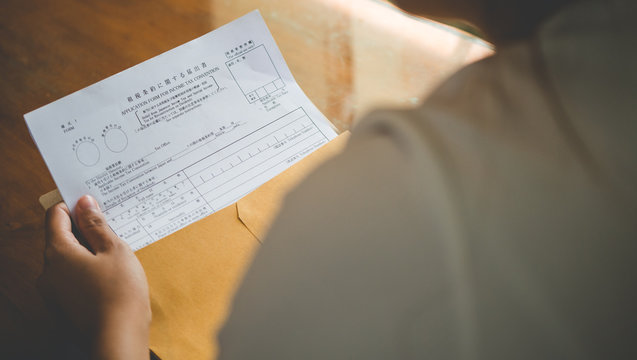 Women are opening an envelope document with japan tax document contract in business and taxation concept,vintage style .