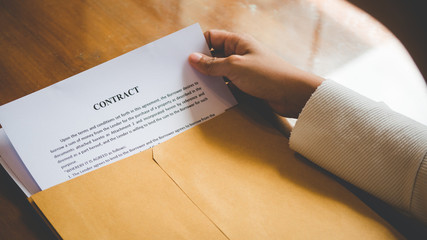 Women are opening an envelope document about signing a contract in business and sign contract concept,vintage style .