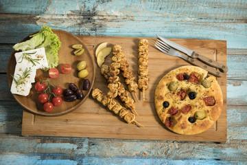 gegrillte Fleischspiesse, mediterranes Ofenbrot mit Oliven und getrockneten Tomaten, Schafskäse mit Rosmarin und Salatblättern garniert, Studio