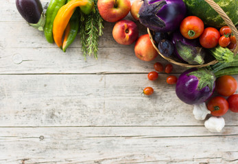 Fresh summer vegetables, collected in a basket of wicker, on a old wooden background.