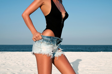 Beautiful woman in black swimsuit and jeans shorts on the beach.