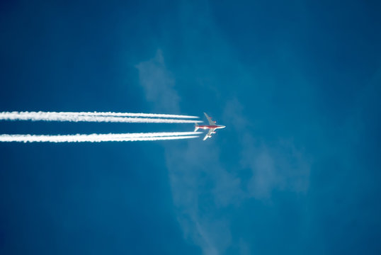 Silhouette of plane flying against the blue sky. A trail of smoke behind