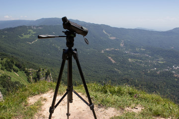 Traveller looking the nature from the high mountain with spotting scope, binoculars tripod