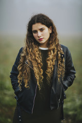 Portrait of young woman with very long curly hair and leather jacket
