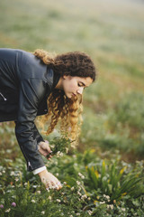 Side view of curly young woman gathering wildflowers in autumnal meadow