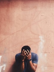 Portrait depressed despaired young man hiding his face