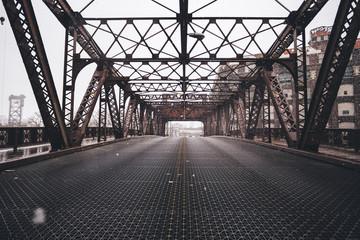 Road through metal bridge tunnel while snow is falling