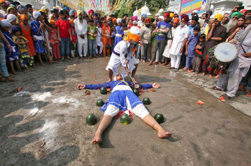 A Sikh man with his eyes covered by a cloth breaks watermelons closely placed around performer as they practise Gatkha in Amritsar