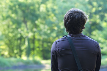 A rear view of a lonely young man looking at nature with a blurred background