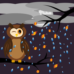A brown owl screwed up his eyes while sitting on the branches of a tree with flying leaves, against the backdrop of an autumnal landscape, the sky was covered with clouds, the rain