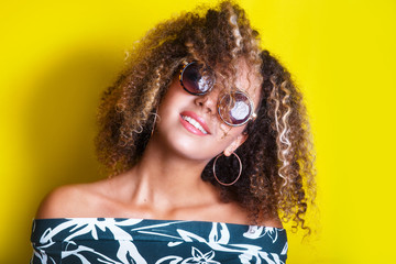 portrait indoors of a young afro american woman in sunglasses. Yellow background. Lifestyle. Casual clothing