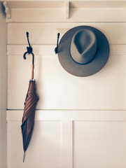 Old mans Tribly hat and umbrella hung on hall stand