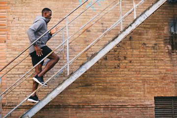 Side view of athlete climbing up stairs in the city.