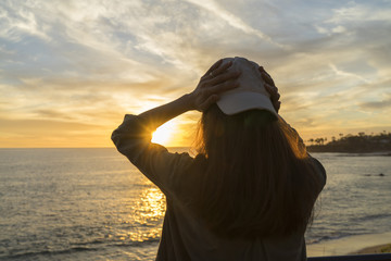 Woman standing backlight sunset lighting back view summer evening beach lens flare