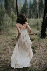 Adventurous bride in long bohemian dress walking through forest in Yosemite on her elopement