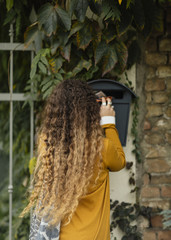 Rear sigh of long haired curly girl taking mail from her mailbox