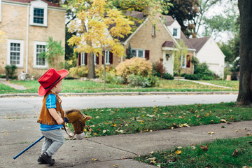 Toddler in cowboy costume riding a toy horse