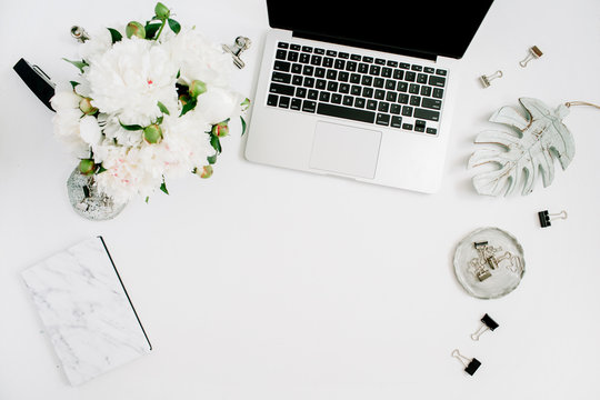 Flat lay home office desk. Female workspace with laptop, white peony flowers bouquet, accessories, marble diary on white background. Top view feminine background.