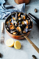 Cooked mussels in a copper pot.