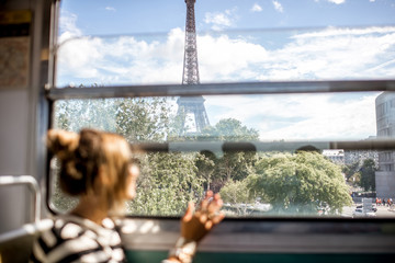 Young woman looking on the Eiffel tower through the train window in Paris. Image focused on the background