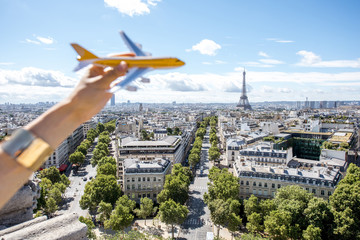 Holding a toy airplane on the Paris cityscape background. Air connection and tourism concept in the capital of France. Airplane is out of focus