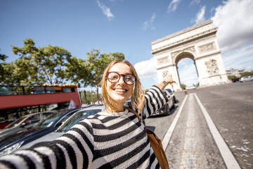 Young woman tourist making selfie portrait with famous Triumphal Arch on the background in Paris