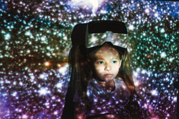 Dreamy little girl in multicolored lights with VR headset