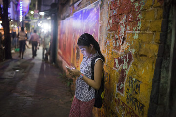 Teenage girl browsing and texting internet at urban street at night